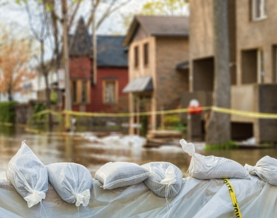 Flooding on a residential street in the City of Ottawa with a sandbag barrier in front of homes.